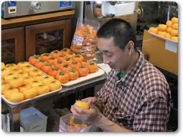 柿の皮をむく岩井店長